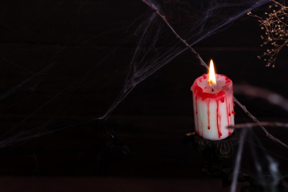 Antique candelabra with melting candle and spider web on black background.